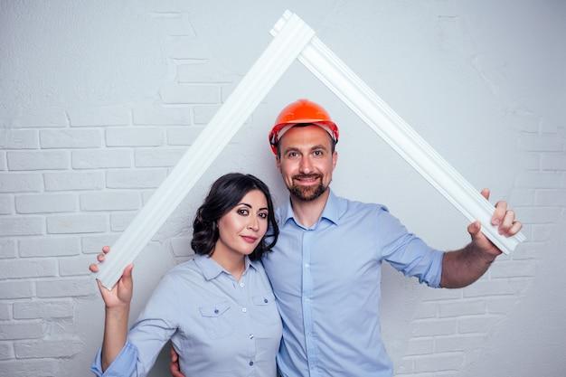 Homem bonito de família feliz no capacete de segurança do capacete de construção e uma mulher encantadora juntos estão construindo a casa do telhado. conceito de compra de um apartamento aconchegante e aconchegante por jovens recém-casados.