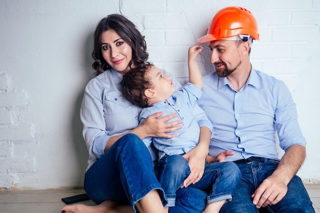 Homem bonito de família feliz no capacete de segurança e mulher encantadora e seu filho pequeno sentado no chão contra uma parede branca. conceito de compra de apartamento de casa de reparos por uma família jovem.