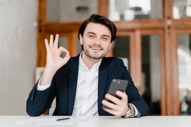 Homem bonito de fato usa telefone no escritório