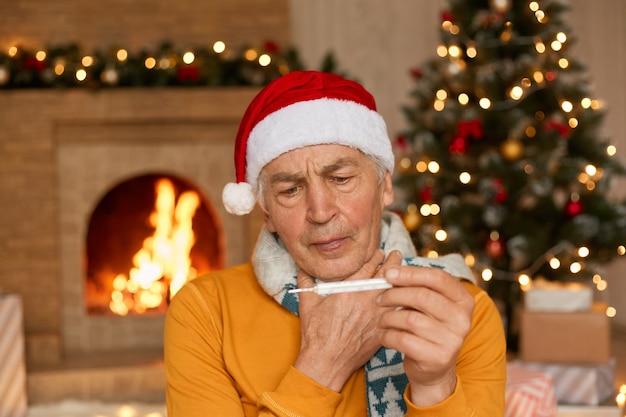 Homem bonito de meia-idade com chapéu de papai noel, cachecol e macacão