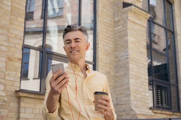 Homem bonito de meia-idade segurando um celular, bebendo café e lendo notícias