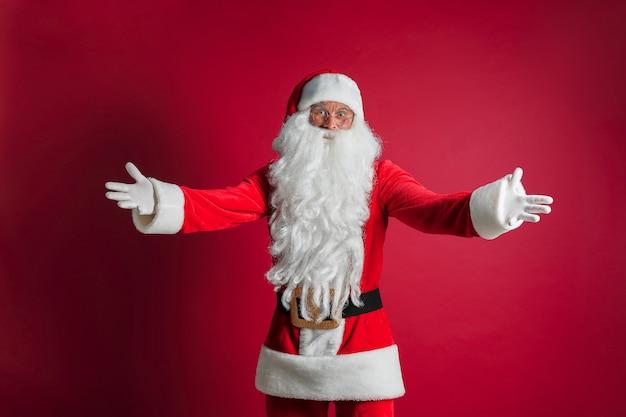 Homem bonito de meia idade vestindo traje de papai noel em pé sobre parede vermelha isolada, sorrindo alegre com os braços abertos como boas-vindas amigáveis, saudações positivas e confiantes