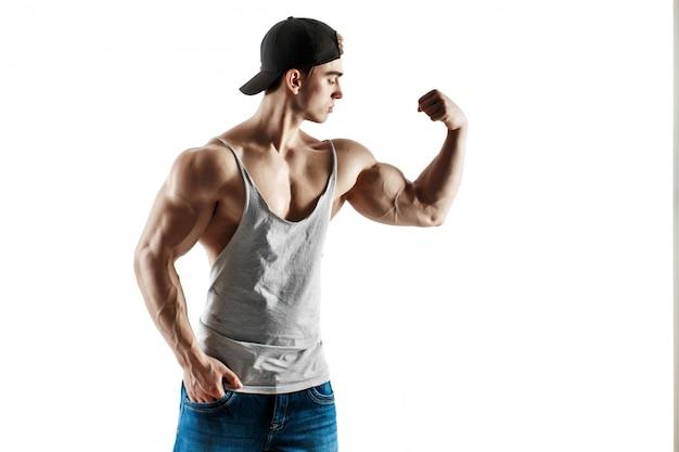 Homem bonito de nível super alto muscular no boné de beisebol e camiseta posando no fundo branco