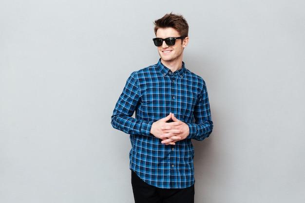 Homem bonito de óculos em cima de parede cinza