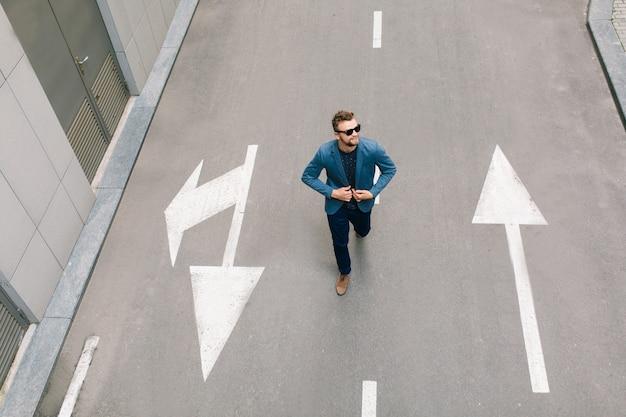 Homem bonito de óculos escuros caminhando na estrada