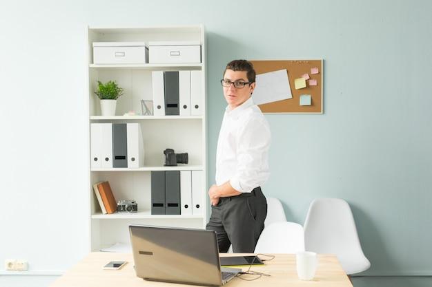 Homem bonito de óculos está no escritório perto de um computador e sorrindo.