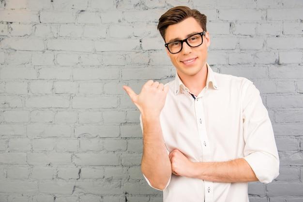 Homem bonito de óculos gesticulando no fundo da parede cinza