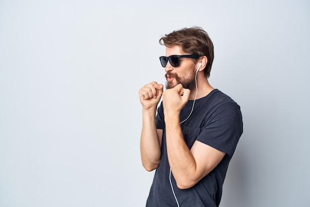 Homem bonito de óculos ouvindo música em fones de ouvido isolados de fundo