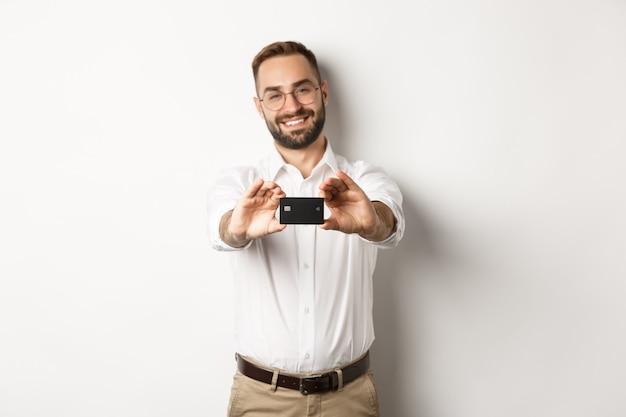 Homem bonito de óculos segurando um cartão de crédito, sorrindo satisfeito, em pé