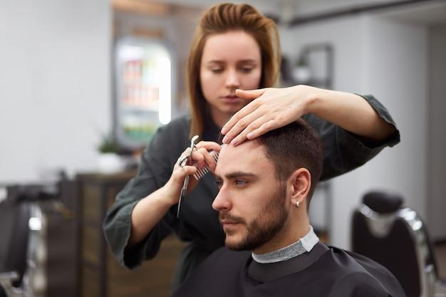 Homem bonito de olhos azuis sentado na barbearia. mulher de cabeleireiro hairstylist cortando o cabelo dele. barbeiro feminino.