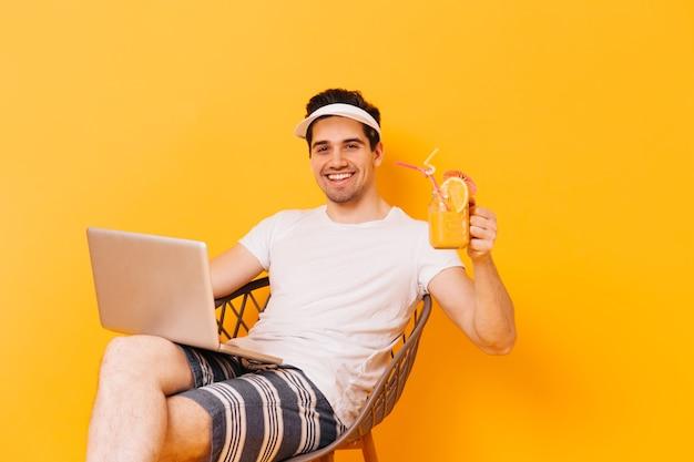 Homem bonito de olhos castanhos com roupa de praia levantou um copo de suco e sorri enquanto trabalhava no laptop.