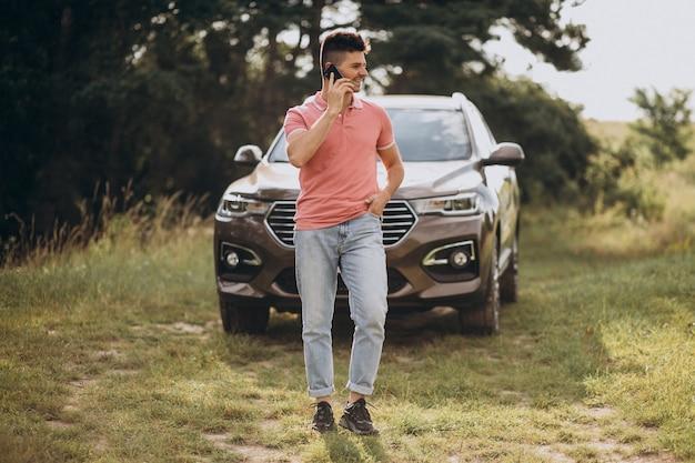 Homem bonito, de pé ao lado de seu carro na floresta