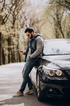 Homem bonito, de pé ao lado do carro no parque