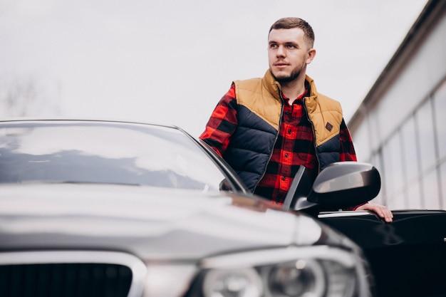 Homem bonito, de pé ao lado do carro