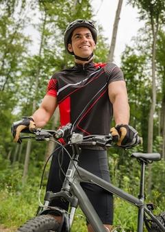Homem bonito, de pé com a bicicleta perto da floresta.