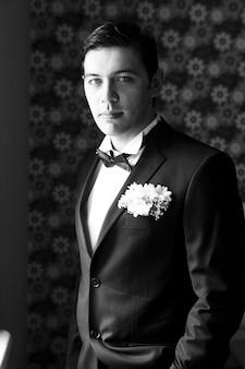 Homem bonito, de pé e olhando no terno do casamento. preto e branco
