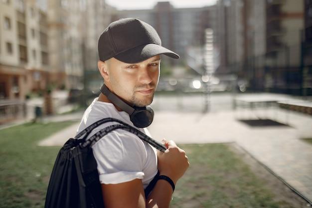 Homem bonito, de pé em um parque com fones de ouvido