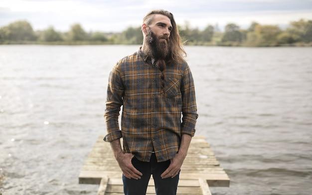 Homem bonito, de pé em um píer de madeira