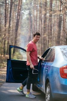 Homem bonito, de pé na estrada perto da porta aberta do seu carro.