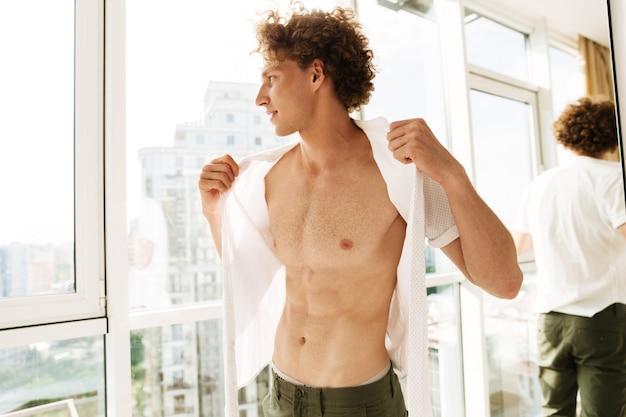 Homem bonito, de pé perto da janela dentro de casa