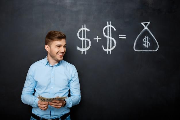 Homem bonito, de pé sobre o quadro-negro com o conceito de dólar desenhado