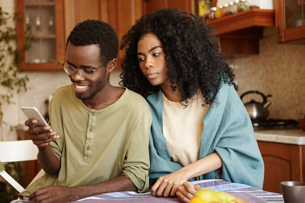 Homem bonito de pele escura navegando nas mídias sociais no smartphone, com um olhar feliz, sem perceber sua esposa sorrateira e suspeita, espionando-o. desconfiança, desonestidade, trapaça e infidelidade