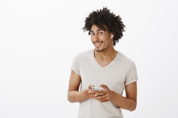Homem bonito de pele escura ouvindo música em fones de ouvido sem fio, curtindo podcast, usando smartphone