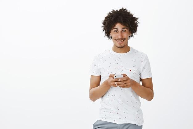 Homem bonito de pele escura usando telefone celular e sorrindo feliz