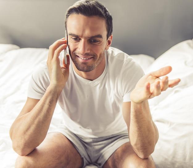 Homem bonito de pijama está falando no telefone celular