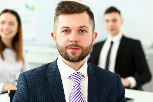 Homem bonito de terno e gravata olha na câmera
