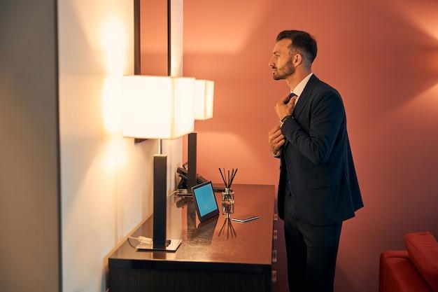 Homem bonito de terno em seu quarto de hotel olhando para o reflexo no espelho enquanto usava uma gravata