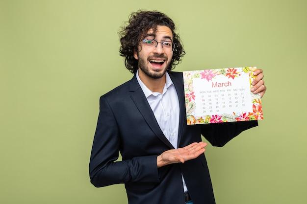 Homem bonito de terno segurando o calendário de papel do mês de março, apresentando o braço da mão, sorrindo, feliz e alegre, comemorando o dia internacional da mulher, 8 de março, em pé sobre fundo verde