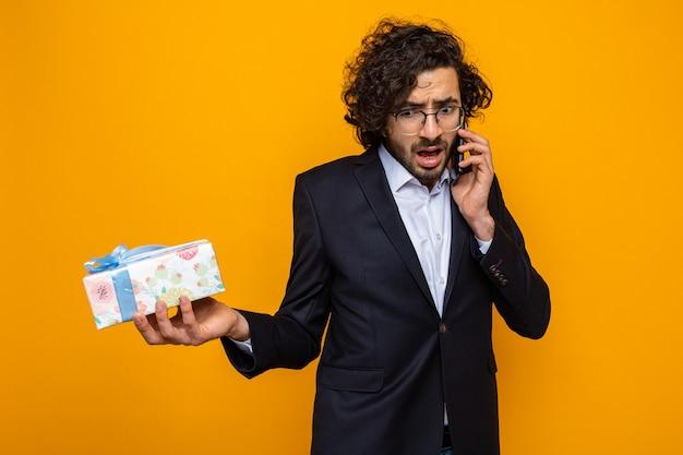 Homem bonito de terno segurando um presente parecendo confuso enquanto fala no celular, comemorando o dia internacional da mulher, 8 de março, em pé sobre um fundo laranja
