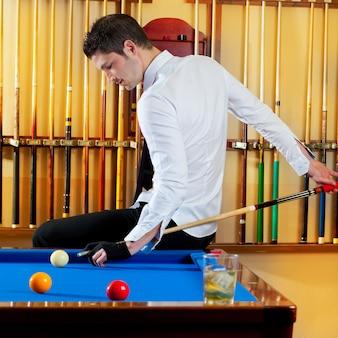 Homem bonito de vencedor de bilhar, brincando com taco e bolas no clube