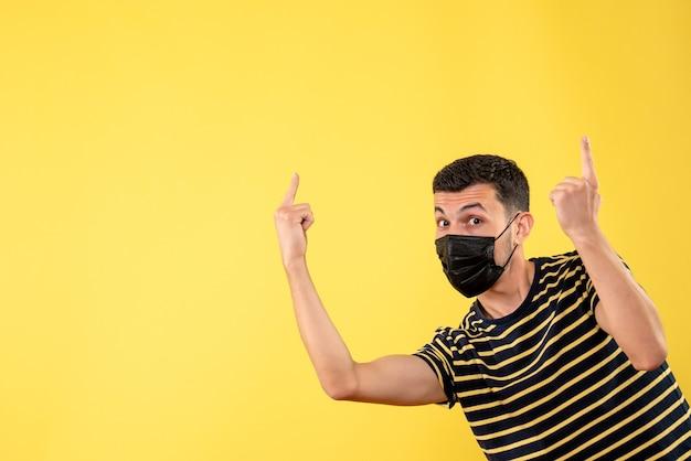 Homem bonito de vista frontal com máscara preta apontando para o teto em fundo amarelo isolado