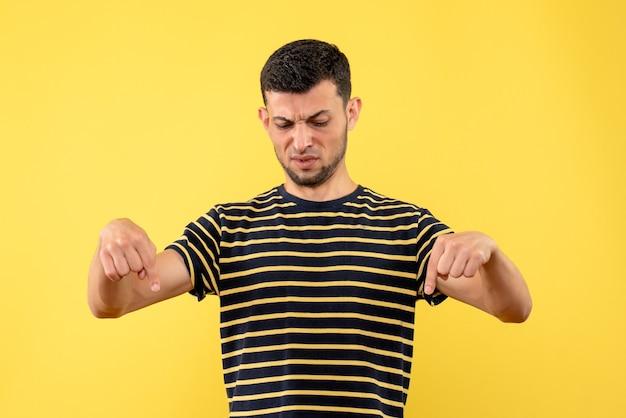 Homem bonito de vista frontal em camiseta listrada em preto e branco apontando para o chão amarelo isolado.