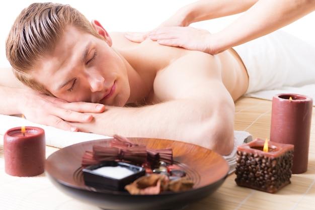 Homem bonito, deitado em um salão de spa, desfrutando de uma massagem profunda nas costas.