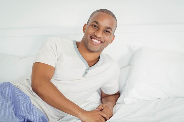 Homem bonito, deitado na cama, sorrindo para a câmera