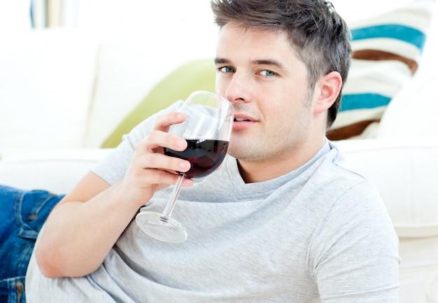 Homem bonito deitado no chão bebendo vinho