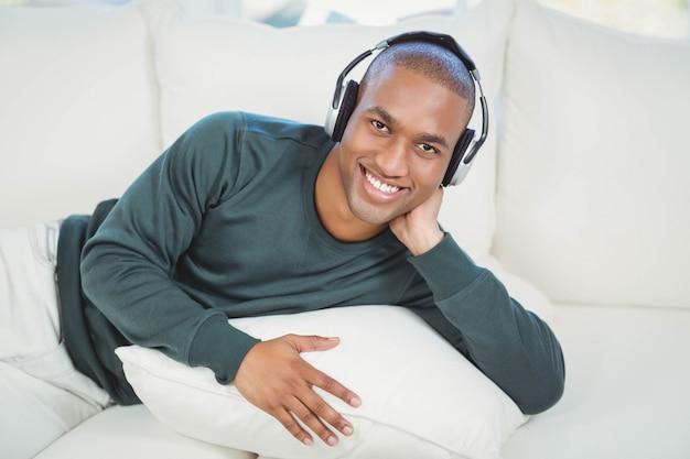 Homem bonito deitado no sofá com fones de ouvido sorrindo para a câmera