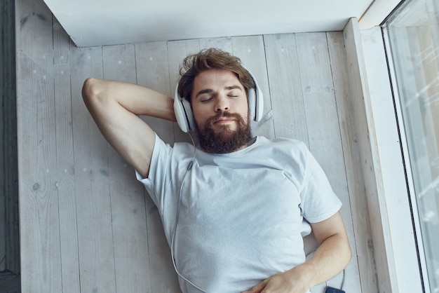 Homem bonito, deitado perto da janela, usando fones de ouvido da moda. foto de alta qualidade