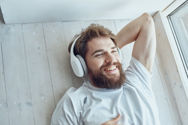 Homem bonito deitado perto da janela usando fones de ouvido hipster