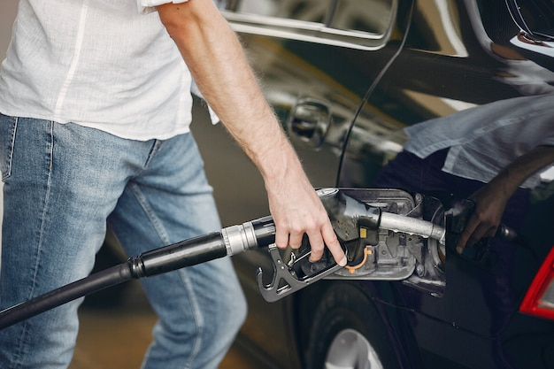 Homem bonito derrama gasolina no tanque do carro