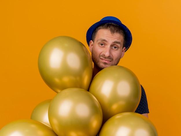 Homem bonito desapontado com chapéu de festa azul segurando balões de hélio isolados na parede laranja