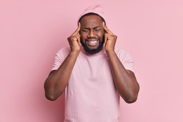 Homem bonito descontente com barba espessa sofre de uma enxaqueca insuportável e mantém os dedos nas têmporas para revelar a dor cerrar os dentes veste uma camiseta casual e poses de chapéu sobre a parede rosa claro