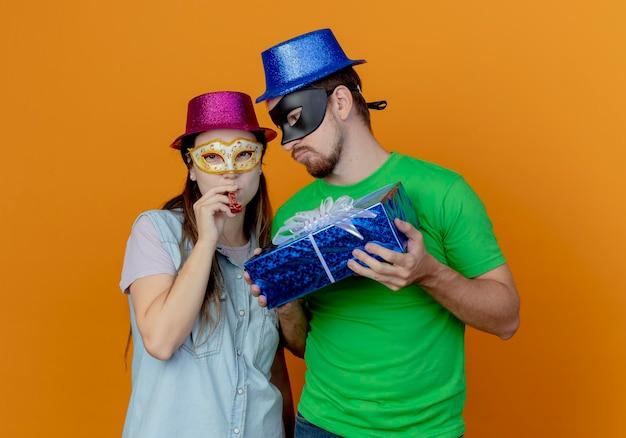 Homem bonito descontente com chapéu azul usando máscara de máscara, segurando uma caixa de presente, olhando para uma jovem alegre, usando chapéu rosa e máscara de máscara, soprando apito olhando para frente