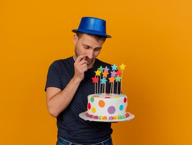 Homem bonito descontente com chapéu de festa azul segura e olha para um bolo de aniversário isolado na parede laranja com espaço de cópia