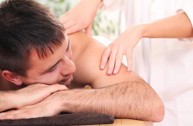 Homem bonito, desfrutando de procedimento de massagem