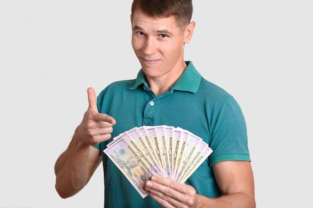 Homem bonito detém muitos dólares, indica em dinheiro, feliz em ganhar muito, sendo rico, vestido com camiseta casual