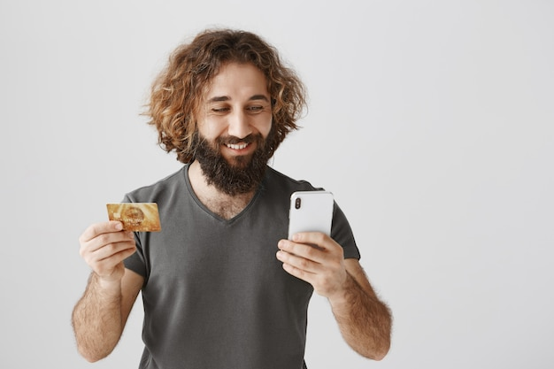 Homem bonito do oriente médio fazendo compras online, segurando um cartão de crédito e um celular
